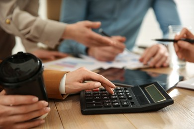 Woman using calculator at table in office during business meeting, closeup. Management consulting