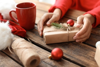 Woman with Christmas gift box at wooden table
