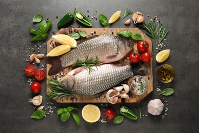 Fresh raw crucian carps and ingredients on grey table, flat lay. River fish