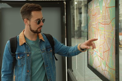 Young man with backpack near public transport map at bus stop