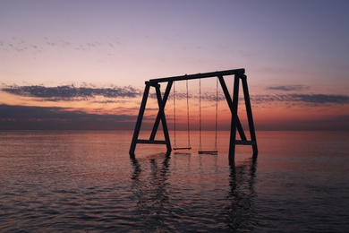 Picturesque view of swing in water on sunrise