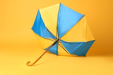 Broken bright umbrella with wooden handle on yellow background