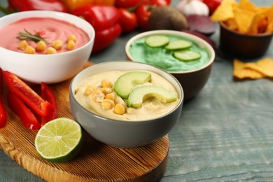 Different kinds of tasty hummus with ingredients on light blue wooden table