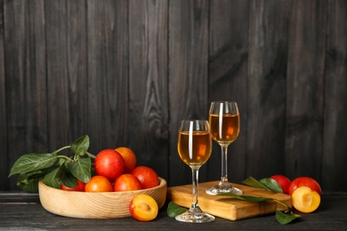 Delicious plum liquor and ripe fruits on black wooden table. Homemade strong alcoholic beverage