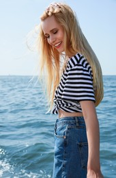 Beautiful young woman near sea on sunny day in summer