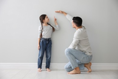 Father measuring little girl's height near light grey wall indoors