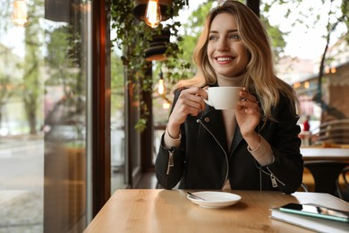Young woman with cup of coffee at cafe in morning