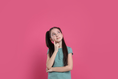 Portrait of pensive little girl on pink background. Thinking about answer for question