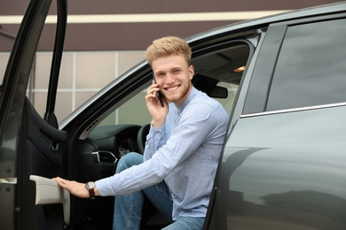 Young handsome man talking on phone while opening car door