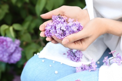 Young woman with blossoming lilac outdoors on spring day