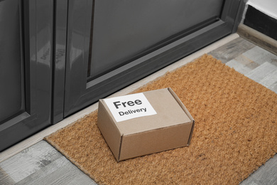 Parcel with sticker Free Delivery on rug indoors. Courier service