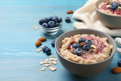 Tasty oatmeal porridge with toppings on light blue wooden table. Space for text