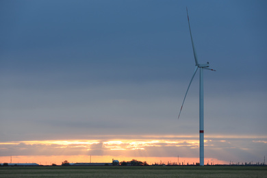 Beautiful view of field with wind turbine at sunset. Alternative energy source