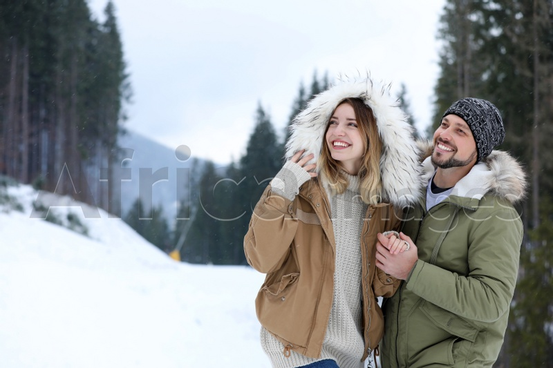 Happy couple near conifer forest on snowy day, space for text. Winter vacation