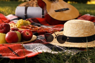 Straw hat, glasses and different snacks for summer picnic on plaid outdoors