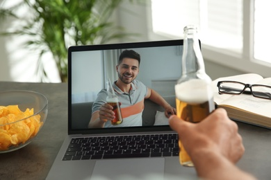 Friends drinking beer while communicating through online video conference at home. Social distancing during coronavirus pandemic