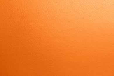 Texture of orange leather as background, top view