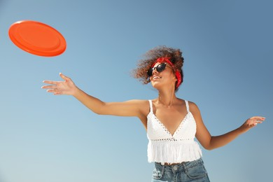 Happy African American woman throwing flying disk against blue sky on sunny day