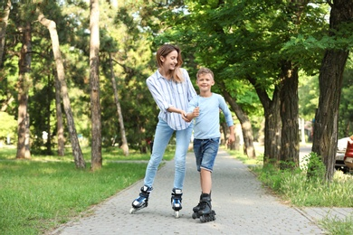 Mother and son roller skating in summer park