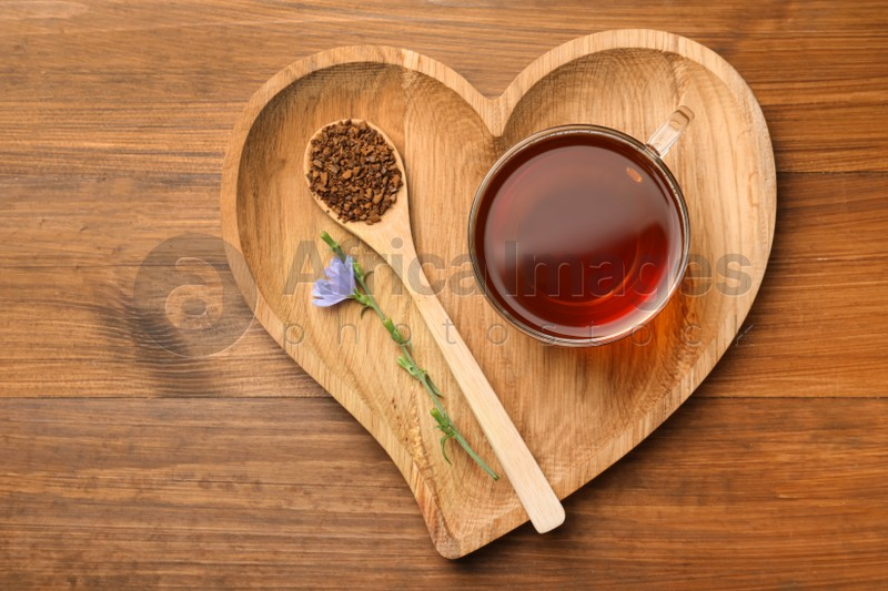 Cup of delicious chicory drink, granules and flower on wooden table, top view