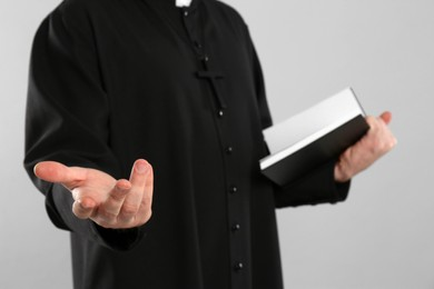 Priest with Bible praying on grey background, closeup