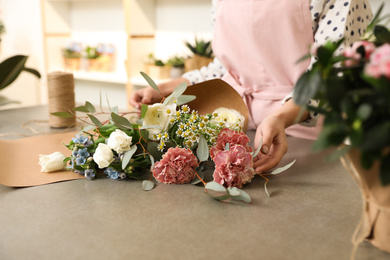 Florist making bouquet with fresh flowers at table, closeup