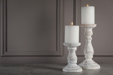 Elegant candlesticks with burning candles on grey table. Space for text