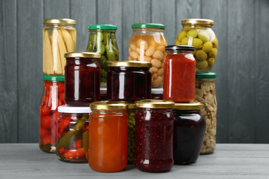 Glass jars with different pickled foods on grey wooden background