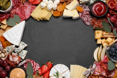 Frame of assorted appetizers on black background, flat lay. Space for text