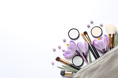 Makeup products, flowers and cosmetic bag on white background, top view