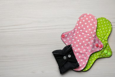 Reusable cloth menstrual pads on white wooden table, flat lay. Space for text