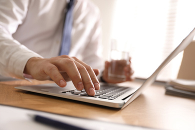 Man working with laptop in office, closeup of hand