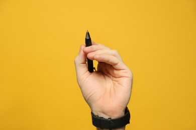 Left-handed man holding pen on yellow background, closeup
