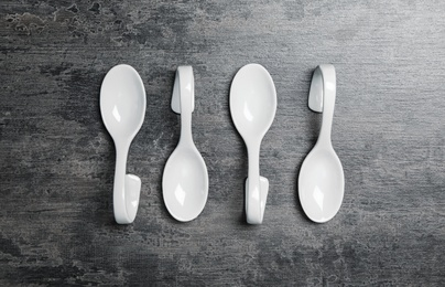 White spoons on grey table, flat lay. Cooking utensils