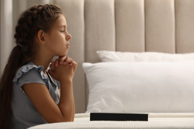 Cute little girl praying over Bible in bedroom. Space for text