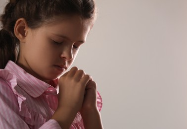 Cute little girl with hands clasped together praying on grey background. Space for text