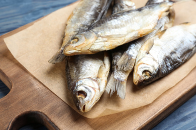 Tasty dried fish on blue wooden table, closeup