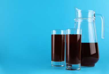 Delicious homemade kvass in glasses and jug on light blue background. Space for text
