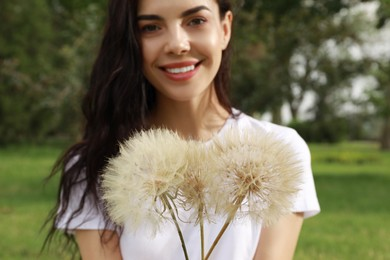 Beautiful young woman with large dandelions in park, focus on flowers. Allergy free concept