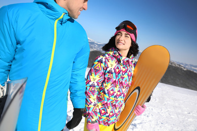 Couple with snowboards at ski resort. Winter vacation