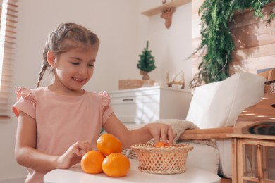 Cute little child with fresh tangerines at home