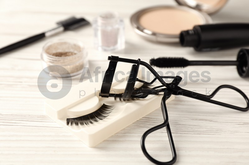 False eyelashes and curler on white wooden table, closeup