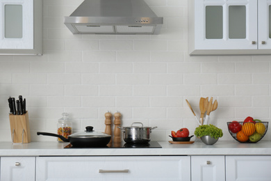 Counter with set of dishware, utensils and products in stylish kitchen interior