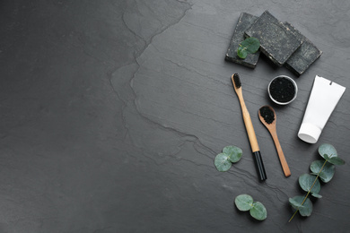 Flat lay composition with bamboo toothbrush on black stone table. Space for text