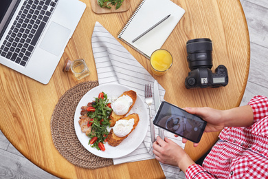 Food blogger taking photo of her lunch at wooden table, above view