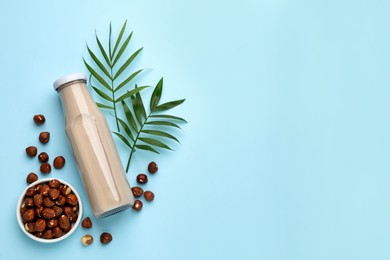 Bottle of vegan milk and hazelnuts on light blue background, flat lay. Space for text