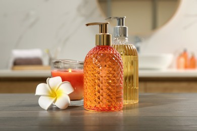 Glass dispensers with liquid soap, plumeria flower and candle on wooden table in bathroom