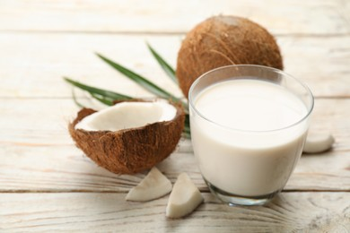 Delicious vegan milk and coconuts on white wooden table, closeup