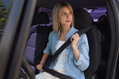 Woman fastening safety belt on driver's seat in car