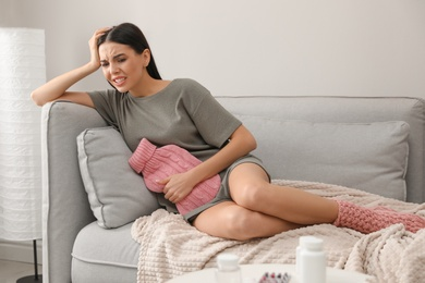 Woman using hot water bottle to relieve menstrual pain on sofa at home